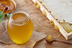Tarro de la miel, polen de la abeja y panales en la tabla de madera Foto de archivo libre de regalías