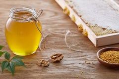 Tarro de la miel, polen de la abeja y panales en la tabla de madera Imágenes de archivo libres de regalías
