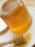 Tarro de la miel y de la cuchara Imagen de archivo libre de regalías