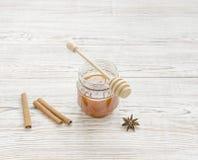 Tarro de la miel y del palillo con las especias Imagenes de archivo