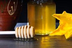 Tarro de la miel y del palillo de madera Imagen de archivo
