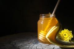 Tarro de la miel y del palillo a la miel en un fondo de madera Imagen de archivo libre de regalías