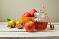 Tarro de la miel y manzanas frescas con la granada en el tablero de madera Imagen de archivo libre de regalías