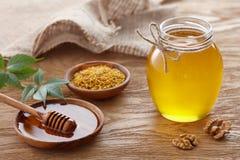 Tarro de la miel y polen de la abeja en la tabla de madera Imagen de archivo libre de regalías