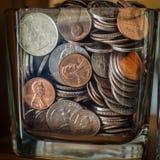 Tarro de los ahorros por completo de monedas Foto de archivo