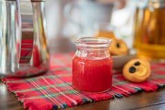 Tarro de mermelada de fresa hecha en casa en la tabla Galletas y tetera en fondo Imagen de archivo