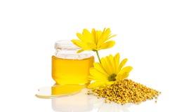 Tarro de miel cerca de una pila de polen y de flor Imagenes de archivo