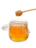 Tarro de miel con el drizzler de madera Fotos de archivo libres de regalías