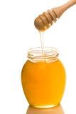 Tarro de miel con el drizzler de madera aislado en el fondo blanco Foto de archivo libre de regalías