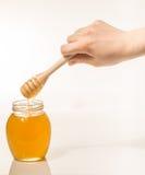 Tarro de miel con el drizzler de madera aislado en el fondo blanco Foto de archivo
