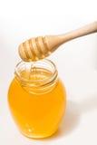 Tarro de miel con el drizzler de madera aislado en el fondo blanco Fotos de archivo libres de regalías