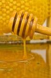 Tarro de miel con el drizzler de madera en fondo del panal Foto de archivo