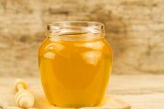 tarro de miel con el drizzler en fondo de madera Imágenes de archivo libres de regalías