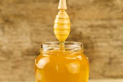 tarro de miel con el drizzler en fondo de madera Foto de archivo