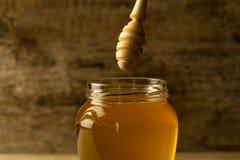 tarro de miel con el drizzler en fondo de madera Imagen de archivo libre de regalías