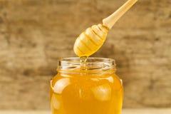 tarro de miel con el drizzler en fondo de madera Fotos de archivo libres de regalías