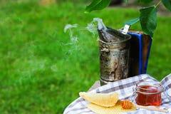 Tarro de miel con la miel del goteo del cazo apicultor de la chimenea outdoors Concepto de la apicultura Imagen auténtica de la f imagenes de archivo