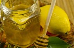 Tarro de miel con un cazo y un limón de madera Fotografía de archivo