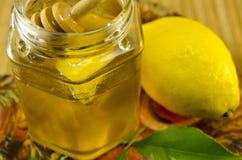 Tarro de miel con un cazo y un limón de madera Imagenes de archivo