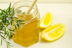 Tarro de miel con una cuchara de madera y un limón cortado Imagenes de archivo