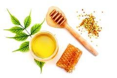 Tarro de miel, de panal y de polen frescos en un fondo blanco Imagen de archivo