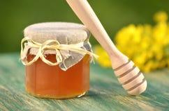 Tarro de miel deliciosa con las flores de la rabina y el cazo de la miel Foto de archivo