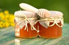 Tarro de miel deliciosa con las flores de la rabina y el cazo de la miel Fotografía de archivo