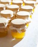 Tarro de miel en el atasco blanco de la tabla Foto de archivo
