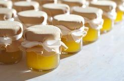 Tarro de miel en el atasco blanco de la tabla Imágenes de archivo libres de regalías