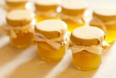 Tarro de miel en el atasco blanco de la tabla Foto de archivo libre de regalías