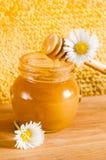 Tarro de miel en el fondo de panales Fotos de archivo