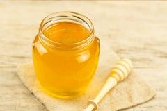 Tarro de miel en tela del yute con el drizzler en fondo de madera Foto de archivo