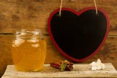 tarro de miel fresca con el drizzler, canela en fondo de madera Foto de archivo libre de regalías