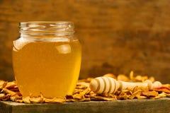 tarro de miel fresca con el drizzler, con las manzanas secadas en fondo de madera Foto de archivo
