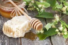 Tarro de miel fresca con las flores del tilo en fondo de madera Foto de archivo