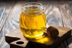 Tarro de miel fresca en una tabla de madera oscura, primer Fotografía de archivo libre de regalías