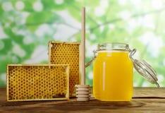 Tarro de miel fresca, marcos con los panales de la abeja y cuchara en superficie de madera Fotos de archivo libres de regalías