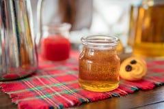 Tarro de miel hecha en casa en la tabla Mermelada de fresa y galletas en fondo Imagenes de archivo