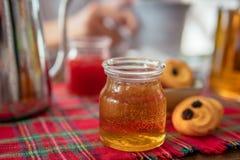 Tarro de miel hecha en casa en la tabla Mermelada de fresa y galletas en fondo Imágenes de archivo libres de regalías