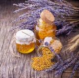 Tarro de miel líquida con lavanda artificial Fotos de archivo libres de regalías