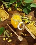 Tarro de miel de la cal, marcos con las células de la abeja, eje y flores del tilo en la tabla Foto de archivo libre de regalías