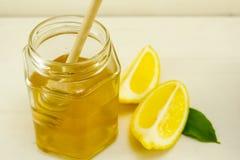 Tarro de miel una cuchara de madera y un limón cortado Imagen de archivo libre de regalías