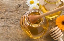 Tarro de miel y de flores en la madera Imagenes de archivo