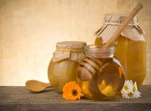 Tarro de miel y de flores en la madera Foto de archivo libre de regalías