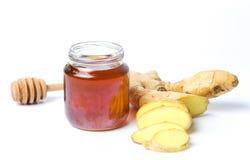Tarro de miel y de jengibres aislados en el fondo blanco Foto de archivo libre de regalías