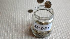 Tarro del ahorro que es llenado de las monedas metrajes