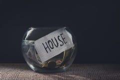 Tarro del dinero con las monedas para una casa Foto de archivo