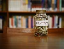 Tarro del dinero de los ahorros de la educación Imágenes de archivo libres de regalías