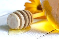 Tarro del primer de la miel en los tablones blancos Imagen de archivo libre de regalías