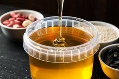 Tarro grande de la miel con el chorrito grueso de la miel desde arriba foto de archivo